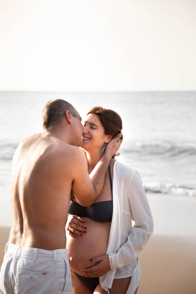 Photo de couple lors d'un shooting de grossesse sur la plage
